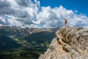 Cet homme sait comment retrouver le moral en levant les bras sur une colline devant un magnifique paysage