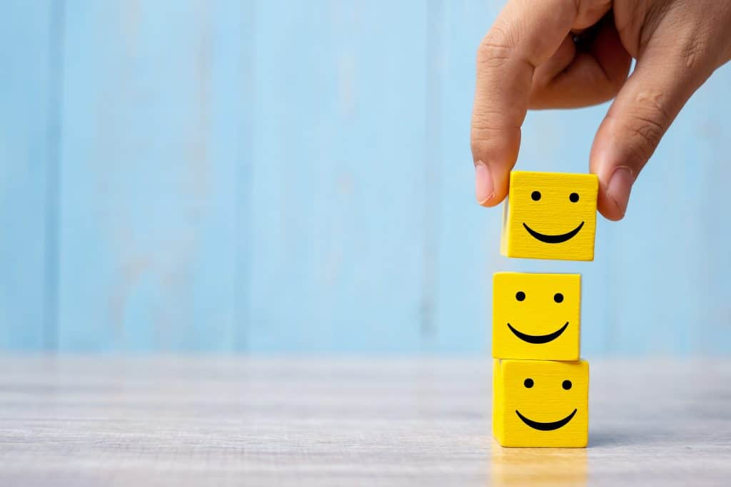 stop à la baisse de moral, comme l'indique cette main qui pose des cubes souriant les un sur les autres