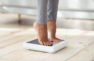 Femme vérifiant si les effets indésirables de la mélatonine sur l'augmentation du poids sont vérifiées en se pesant sur une balance du bout des pieds
