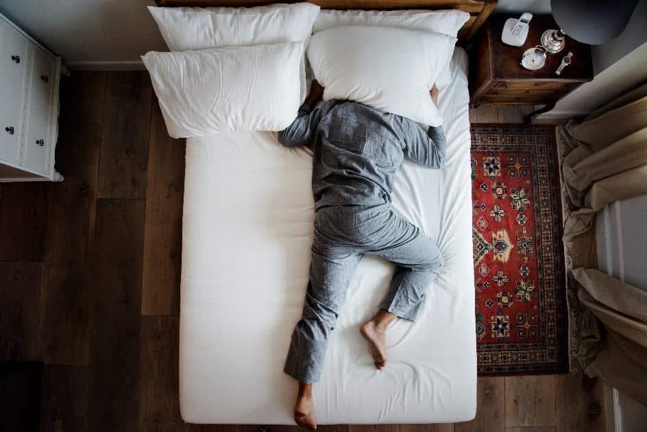 homme dans un lit souffrant d'insomnie