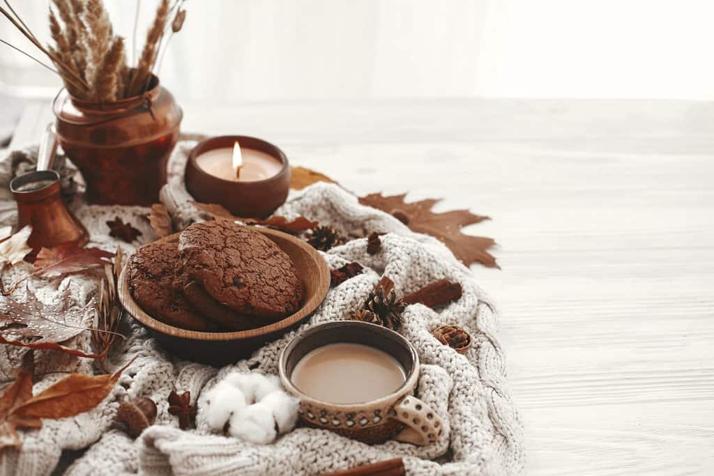 Pour vous aider à stimuler vos hormones de bien-être, le mode de vie Hygge, propose une ambiance confortable. Tasse à café, biscuits au chocolat, bougie et feuilles d'automne composent cette photo