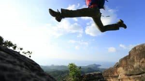 Avoir plus d'énergie comme cette personne qui saute au dessus d'un precipice entre deux rochers