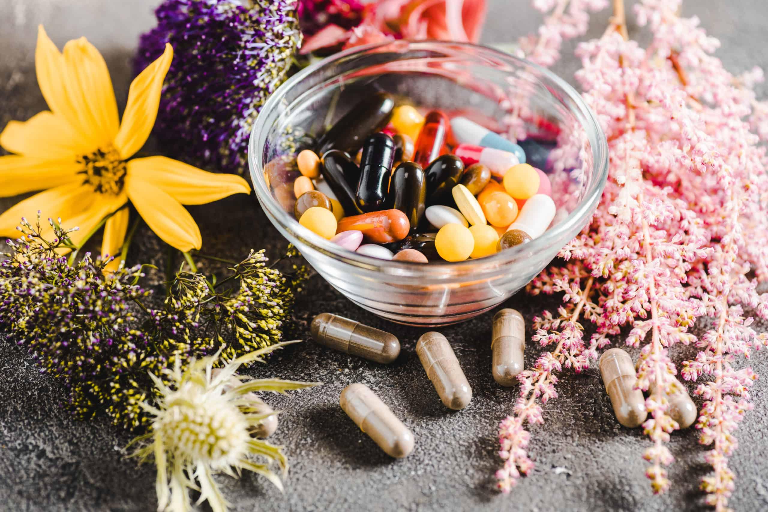 Une séléction des meilleurs actifs de santé naturels pour l'énergie, comme le montre ce bol transparent rempli de gélules et capsules, entouré de fleurs et de plantes médicinales