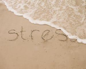 Comment gérer son stress, à l'image de cette vague qui efface le mot stress écrit sur le sable d'une plage