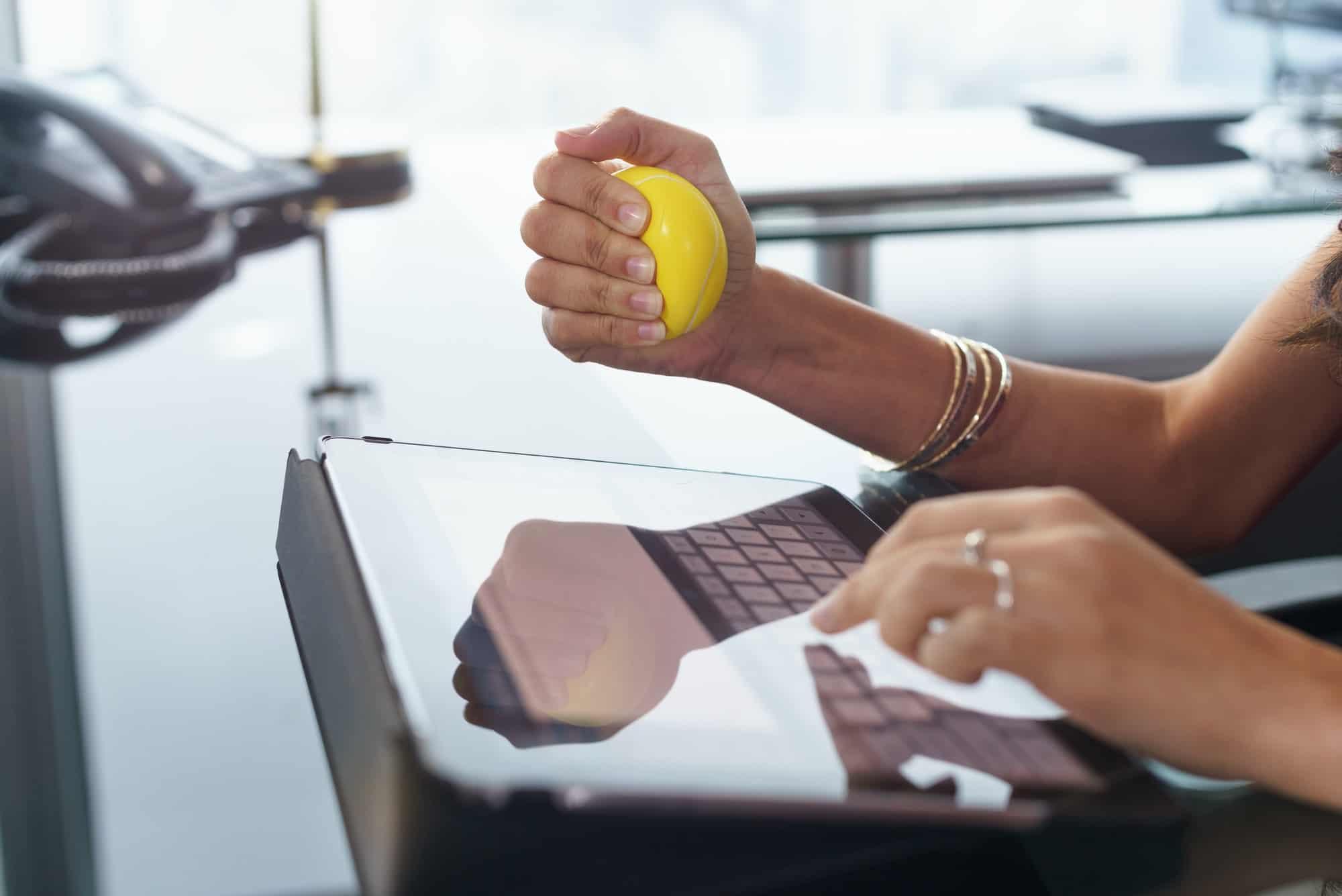 Femme stressé au bureau pressant d'une main une ball anti-stress et tapant un email sur sa tabelle de l'autre main