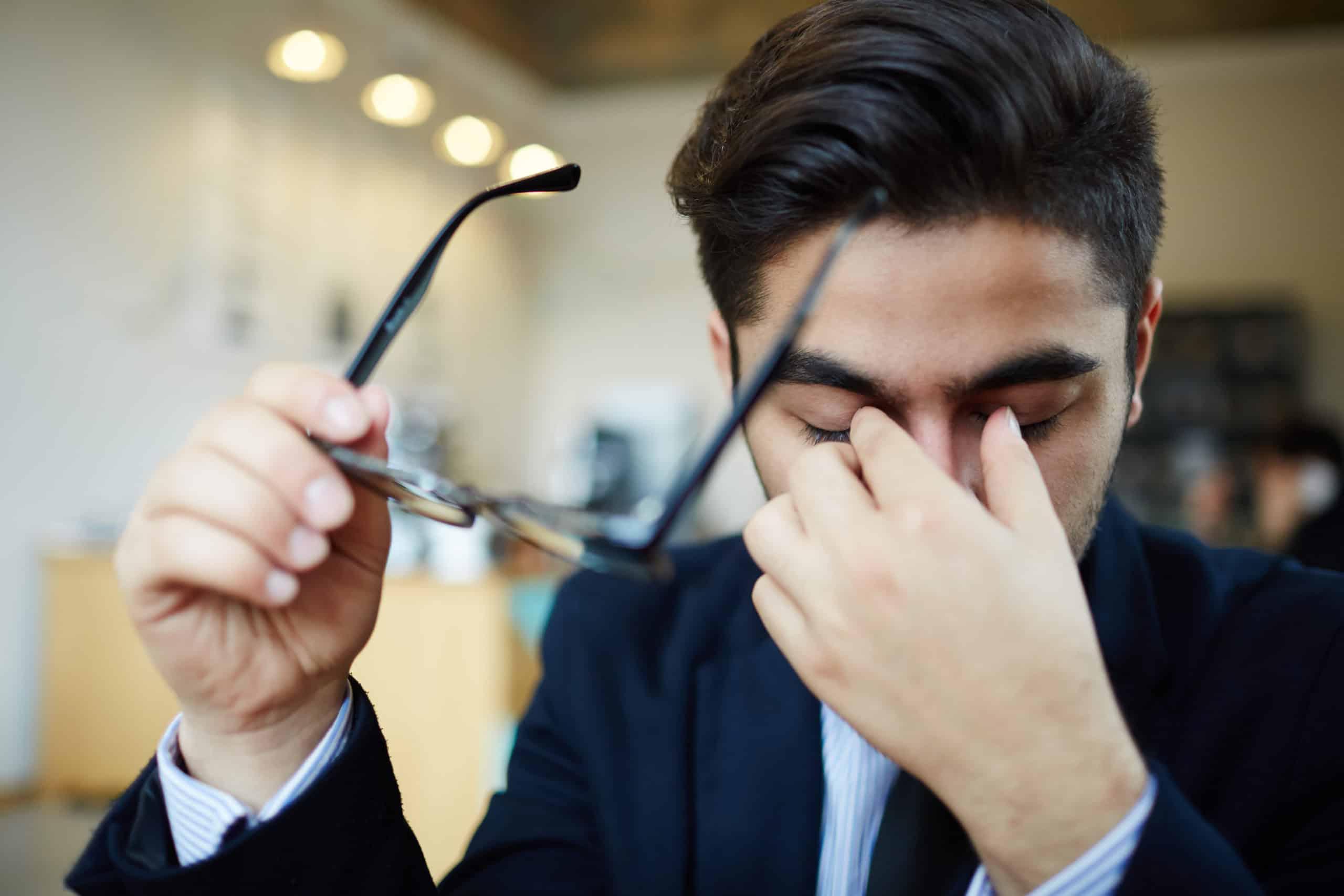 homme tout le temps fatigué au travail, se frottant les yeux